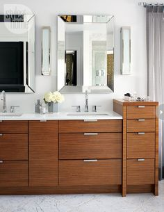 Quarter-sawn walnut with the grain running horizontally adds warmth to pure white quartz countertops. A pair of bevelled mirrors adds a touch of glamour.