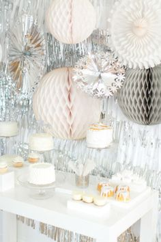 New Year's Eve is the one day your decor theme can incorporate shine, shine and more shine. This party from Style Me Pretty Living features a myriad of shiny silver decorations, anchored by a plain white table with treats.