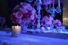 Esferas de flores en la gama de los rosas acompañados por candelabros de cristal
