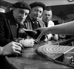 Pouring the first Coke in France...Men looking for the first time a Coca Cola being served, during its arrival in France in 1950. They don't look thrilled about how it looks.