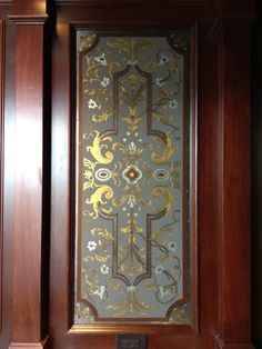 Glass Panel reverse Painted and Gilded set into a Mahogany Paneled wall, Designed and Painted by James Evinczik