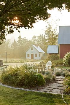 Lobelia, daylilies, nasturtium, and garlic chives surround L.L. Bean Adirondack chairs on the patio, located between the house and the main red barn. Tarr constructed the white field barn to store his tools.   - CountryLiving.com