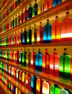 This is one of my favorite pieces ive seen so far. I wonder if the bottles are actually colored or lit from behind. Or maybe filled with the color in liquid from and lit with light. Anyway, I really like the rainbow effect created. Although it isnt in order, I really like it.   An awesome shot. / #colorful #bar #bottles