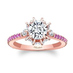 This unique pink sapphire and diamond engagement ring features a prong set round center diamond with marquise diamonds adorning the gallery on the sides of the head. Shared prong set diamonds and pink sapphires embellish the ridges of the rose gold shank for a sophisticated finish.<br /> <br /> Also available in yellow, white gold, 18k and platinum.