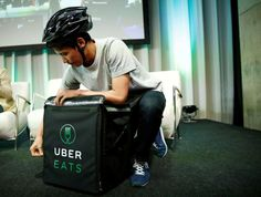 A staff delivers food as he demonstrates a food-delivery service at the launching event of UberEats in Tokyo, Japan, September 28, 2016.