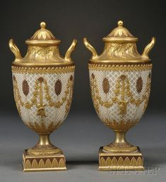 Pair of Wedgwood Gilded and Bronzed Queen's Ware Vases and Covers, England, c. 1880, each with two handles and decorated with a variety of foliate borders to either side of vine festoons with ribbon drops and trophies.