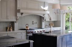Blue paint on two kitchen island's base breaks up an expanse of white cabinetry and serves as the focal point in a transitional kitchen design.