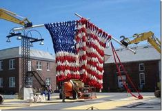 The Knitting Machine is just one of artist Dave Cole's large scale projects that consist of ambitiously knitting unconventional materials. In this particular piece Cole uses two excavation tractors equipped with 20′ knitting needles to assemble a giant American flag in time for the 4th of July (2005).
