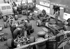 Gold Leaf Team Lotus mechanics working on the 49B's and 63's in the paddock, Silverstone, British Grand Prix 1969.