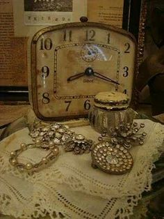Tiempo Me:  Really like this...weathered antique clock w/ lace & jewels & pretty jar or embroidered something lid?  (can't white see what is)