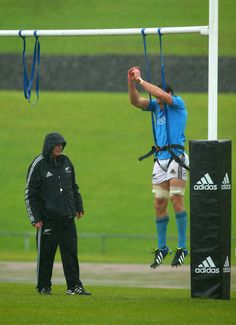 Jeremy Thrush of the All Blacks is watched by forwards coach Mike Cron (L) during a New Zealand All Blacks training session at Trusts Stadium on June 4, 2013 in Auckland, New Zealand.