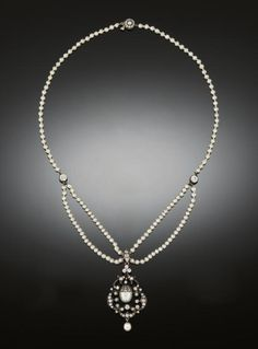 A LATE 19TH CENTURY PEARL AND DIAMOND NECKLACE  The central pearl drop with old-cut diamond cap suspended within an old-cut diamond openwork scroll design frame with trefoil surmount and single pearl drop, to pearl twin row swags and single row necklace with old brilliant-cut diamond single stone twin spacers and half-pearl and diamond cluster clasp
