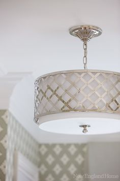 A modern drum-shade ceiling light in the master bath.