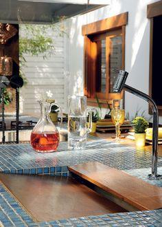 Ao lado da churrasqueira, a pia recebeu tábuas de madeira envernizada. Jarras de vidro da Suxxar. Projeto de José Luiz Lemos.