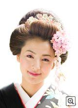 「新日本髪」。髪の長さにかかわらず結うことができる、日本髪風の髪形。昭和20年代に考案された。びんつけ油も使わず逆毛やすき毛を駆使して日本髪風に仕上げる。昔の日本髪の雰囲気を真似たもので、油を使わずに洋髪の技術でつくられています。