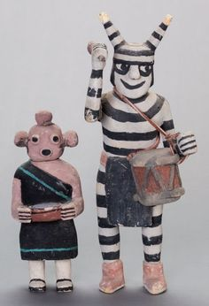 54015 TWO HOPI COTTONWOOD KACHINA DOLLS Jimmy Koots c. 1950  one representing Koyemsi, the mudhead kachina, her hands grasping a bowl, wearing a traditional black dress, and case mask with typical circular features; the other, a Koshari, or clown kachina, with drum suspended on hide, his right arm raised and grasping a drumstick, wearing striped costume, including a horned cap over traditional coiffure  Heights: 7 and 10 ½ inches < Makka Pakka!! :D