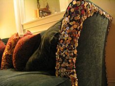 Buttons sewn on a couch, to cover cat scratches, and discourage clawing! What a great idea!