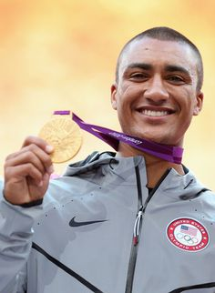 Ashton Eaton shows off his Olympic gold medal after winning the decathlon in the 2012 London Games (Photo by Ezra Shaw/Getty Images)