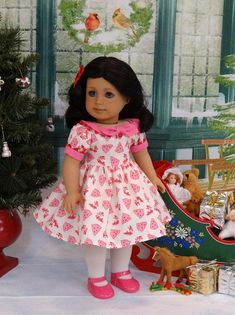 This adorable retro style dress is made of a charming reproduction reindeer and Christmas tree print in pink and red on ivory cotton. The bodice features a boat neck style with pink cotton collar embellished with red rick rack and a tabbed decorative bow fastened in place with a