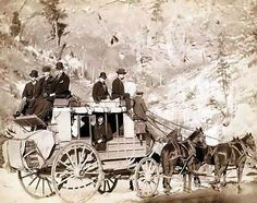 """""""The Deadwood Coach""""  It was made in 1889 by Grabill, John C. H., photographer.    The photo illustrates Side view of a stagecoach; formally dressed men sitting in and on top of coach."""