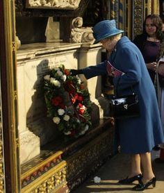 Queen Elizabeth II placing flowers on Isaac Newton's grave in Westminster Abbey