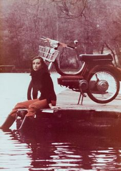 A friend's mother in her 20s posing with a Vespino moped in a lake dock circa 1980