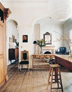 Rustic floors and white walls. Desk in the middle of an archway.