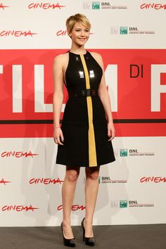 Jennifer Lawrence  chose a pair of embellished black Saint Laurent platform pumps to complete her look. Brand: Yves Saint Laurent cut a very stylish figure at the 'Catching Fire' Rome photocall in this black Proenza Schouler dress featuring metal embellishments and a yellow stripe down the front. Brand: Proenza Schouler