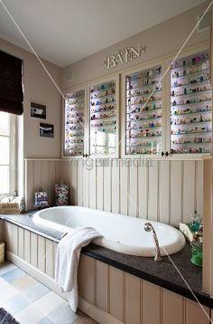 Living4media   Sammlung Farbiger, Winziger Fläschchen In Beleuchteten  Glasvitrinen über Der Eingebauten Badewanne Mit Holzverkleidung