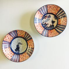 Small Red and blue glazed porcelain plates with Japanese influenced illustration. Also equipped for wall display with copper wire hanger.