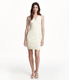 Kurzes, ärmelloses Jerseykleid. Modell mit drapiertem Vorderteil im Wickelschnitt und tiefem V-Ausschnitt im Rücken. Taillennaht. Gefüttert.