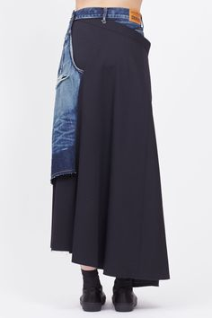 Denim skirt with distressing and fading throughout, asymmetrical wool panel attached at interior, slit at side, raw edges. Dry clean only.