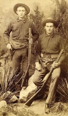 """TWO YOUNG COWBOYS """"GUNS, BOWIE KNIVES, RIFLES"""" ca. 1880 These two Cowboys have all the accouterments for the Wild West and the location """"New Mexico, Territory"""". Man on left: Over and under shotgun, Bowie knife, cartridge belt with six-shooter. Man on right: Winchester, Bowie knife, cartridge belt with six-shooter and also long rifle cartridge belt. These cowboys are ready for action. Whittick & Son, photographers, Albuquerque, N. M."""
