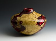 Alan Trout  2013    Size   H: 4.5 in  W: 6.5 in    Burl series. It is a piece or olive cast in a red pigmen resin.