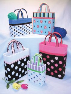 "Tote your craft projects in style!   Fun and fashionable totes featuring polka dots, stripes, floral patterns and butterflies. Largest tote is 9"" wide x 12"" high x 3"" deep; smallest is 5 1/2"" wide x 7"" high x 2"" deep. Made using 7-count plastic canvas and worsted weight yarns."