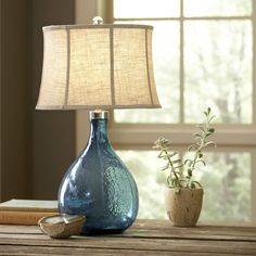 Sapphire Glass Table Lamp | A deep azure glass base makes this glass lamp a statement piece. A curved fabric shade lends it a feminine silhouette.