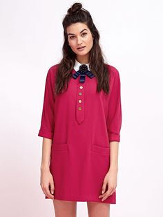Fuchsia shift mini dress with contrasting white collar, gold buttons, and a large removable indigo brooch.  Fabric Composition: 96%…
