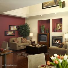 Very Old Living Room With White High Ceilings A Wood Burning Fireplace Open Shelves And Burgundy Paint For The Walls Despite Its Traditional Accents