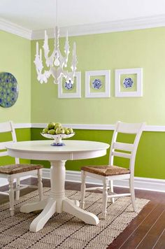 green wall paint and white picture frames are modern dining room wall decoration ideas