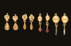 Four Pairs of Roman Gold Earrings, circa 1st-3rd Century A.D.   One pair each with a plain hoop joined to a pelta-shaped shield, with a pendant in the form of a pinecone; another similar pair each with a flanged, drop-shaped pendant; one pair each with a plain hoop joined to a hollow hemisphere, with a voluted pendant, now threaded with a carnelian bead; and another similar but larger pair, each with a pendant, now threaded with green glass beads