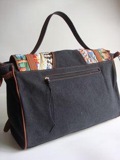 Bolsa feita de lona estonada e detalhe em tecido importado.  Possui divisória interna e bolsos na parte de trás e interno. Alça de mão e transversal