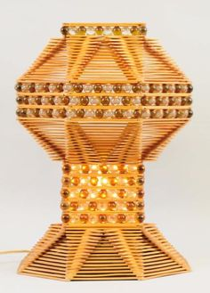 This lamp is composed of Popsicle sticks and glass marbles. Nice composition. Condition (Excellent). Size 15 'T.