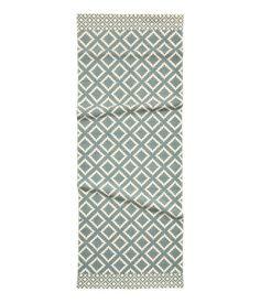 Naturvit/Gråblå. En rektangulär matta i vävd bomullskvalitet med tryckt mönster på ovansidan.
