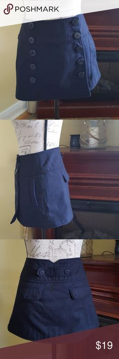 """American Eagle  small dark blue wool mini skirt Waiste 14.5 in the front double to 29 inches total.   Length in back from the top of the waist down to the bottom hem is 13""""   This is a really pretty dark navy blue color this is new without the tags. There are spare buttons still hanging in a plastic baggie from the inside size tag. The pockets in the front are working pockets. The pockets in the back are also working pockets. If you have any questions please ask before purchasing. Thank you…"""