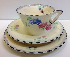 Pink and blue flowers, yellow centres, green leaves on ivory base with pale blue and black trim.   eBay! Jan 2017 GBP33 list BIN