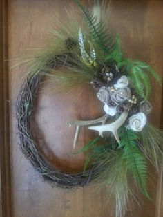 Trying the rustic look.  Deer antlers burlap flowers,  feathers and a birds nest. Grapevine wreath adds the last touch