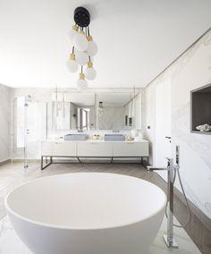 Baño de vivienda en Ibiza, diseñado por Natalia Zubizarreta Interiorismo. Mueble de baño en madera lacada y patas de hierro con lavabos sobre encimera mármol gris. Grifería de pared. Espejos retroiluminados. Paredes en azulejo porcelánico gran formato imitación mármol. Baldosa porcelánica imitación madera en espiga. Bañera exenta resina de Kos. Foseado perimetral en techo retroiluminado. Luminarias suspendidas en dorado y blanco. Ducha doble de obra a medida. Mampara a medida. Hornacinas. Bad Inspiration, Bathroom Inspiration, Ibiza, Interior Exterior, Bathroom Flooring, Bathtub, Instagram Posts, Home, Floors