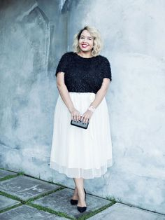 Gabi Gregg of Gabifresh in a white double-layer midi skirt with a black cropped fuzzy shirt and black pumps