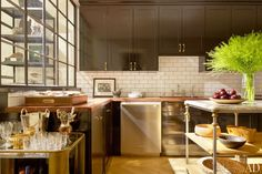 Nate Berkus painted the existing kitchen cabinetry a high-gloss black by Farrow & Ball and added crown molding and brass pulls; the subway-tile backsplash, Electrolux dishwasher, and marble-top island are new. (via Architectural Digest) Painting Kitchen Cabinets, Kitchen Cabinetry, Kitchen Paint, Kitchen Backsplash, Kitchen Dining, Backsplash Ideas, Tile Ideas, Kitchen Decor, Big Kitchen