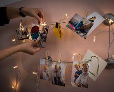 Una persona colgando una foto en un cable de cortina con luces de colores entrelazadas